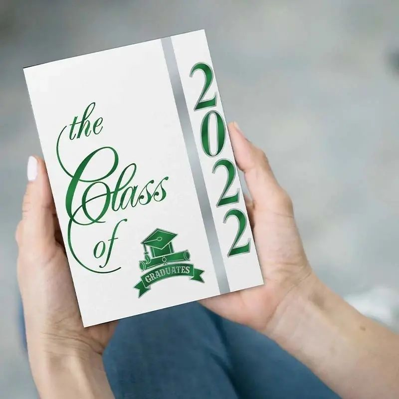 Hands holding a Class of 2021 graduation announcement with green foil.